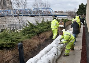Volunteers and city workers place sandbags around the public museum and GVSU as the Grand River continues to rise in downtown Grand Rapids, Mich. Friday, April 19, 2013. (Chris Clark | MLive.com)